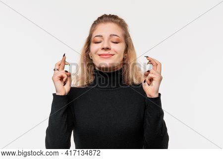 Close Up Blonde Girl With Eyes Closed And Crossing Both Fingers, Feeling Worried Or Hoping For Good