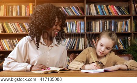 Professional Individual Afro-american Tutor With Long Curly Hair Dictates Text To Blonde Schoolgirl