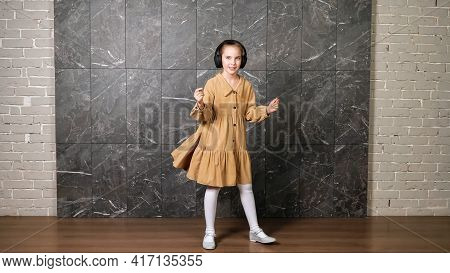 Delighted Active Girl In Brown Dress Dances Wearing Black Headphones Against Designed Marble Wall Su