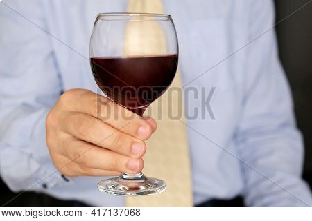 Man In Business Clothes With Glass Of Red Wine In Hand. Corporate Party In Office Or Diplomatic Rece