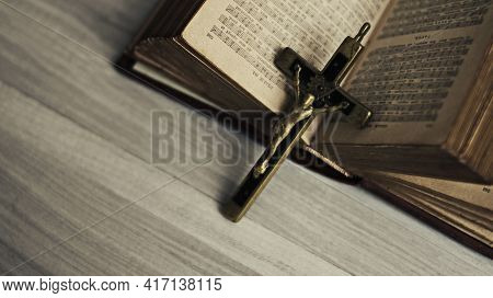 Top View Of Holy Bible Christian Religion Book And Cross Made Of Brass In Antiquity, Vintage, Dark T