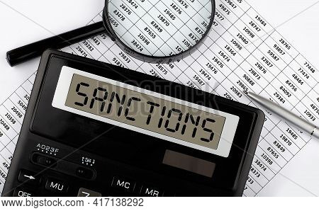 Word Sanctions On A Calculator. Business Concept.