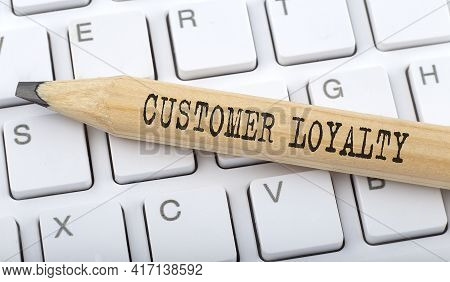Text Customer Loyalty On Wooden Pencil On White Keyboard. Business