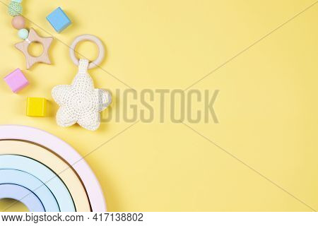 Baby Kid Toys On Yellow Background. Sustainable Early Childhood Development Baby Stuff And Natural P