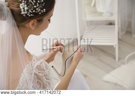 Young Bride Writing On Her Shoe Indoors, Closeup. Wedding Superstition