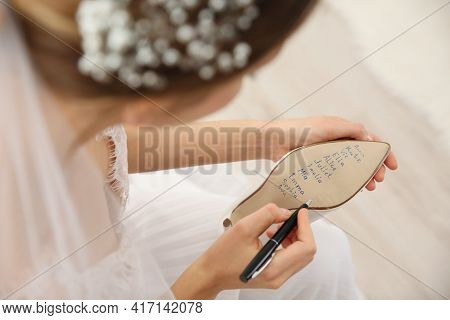 Young Bride Writing Her Single Friends Names On Shoe Indoors, Closeup. Wedding Superstition