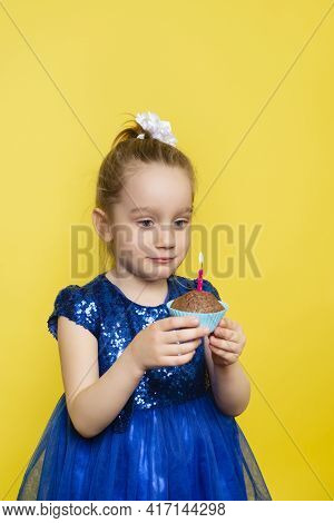 Child Girl Blows Out A Candle On A Cupcake And Makes A Wish. Happy Birthday Or Make A Wish Concept