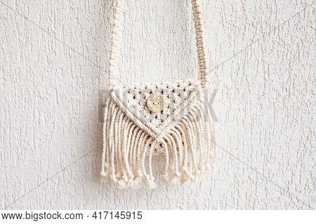 Handmade White Macrame Bag On The White Wall, Eco Friendly. Hobby Knitting Handmade Macrame. Modern