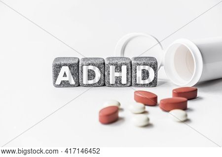Word Adhd Is Made Of Stone Cubes On A White Background With Pills. Medical Concept Of Treatment, Pre