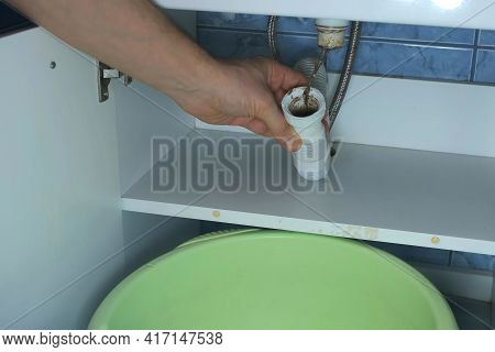 Man Unscrews Pipe At Bottom Of Sink, Clears The Blockage, Hands Closeup. Plumbers Mans Hand Unclogs