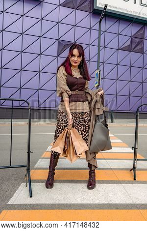 A Beautiful Girl With Shopping Bags Is Walking Along A Pedestrian Crosswalk. Consumerism, Shopping,