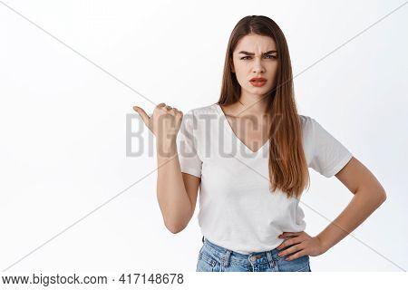 Confused Angry Girlfriend Frowns And Points Aside At Left Copy Space, Shows Something Bad Or Strange