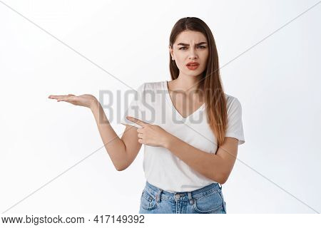 Confused Woman Holding Something Strange In Open Hand, Pointing At Palm With Your Logo Product Again