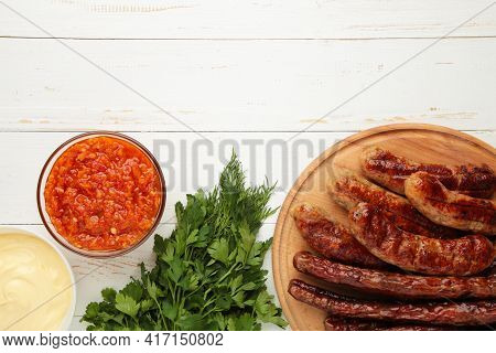 Grilled Sausages On Wooden Board On White Background. Top View