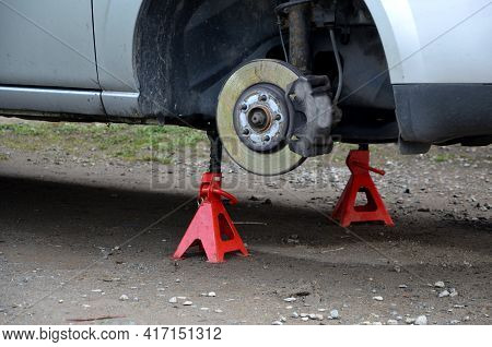 Car Repair At Home In The Yard. The Car Is Without Wheels And The Brake System Is Checked. Red Pyram