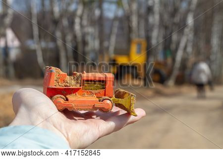 A Toy Model Of A Bulldozer On The Hand Against The Background Of A Real Car A Yellow Bulldozer.