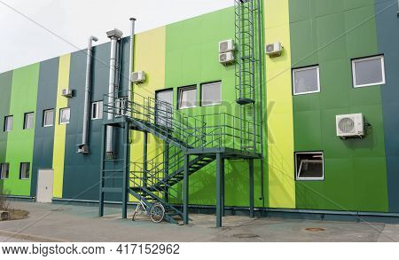 The Back Wall Of The Hypermarket With Iron Fire Escapes, Exhaust And Ventilation Pipes, Windows, Bic