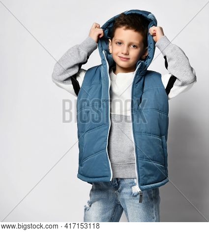 Studio Shot Of Little School Boy In Warm Outwear Vest, Jeans And Sweatshirt Posing For Camera Wearin