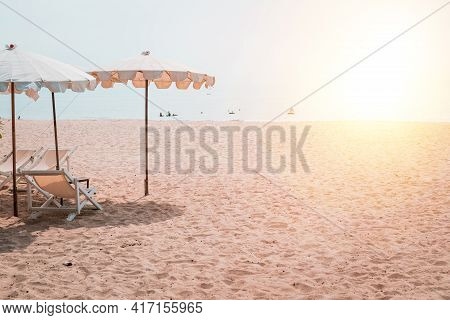 Deckchairs And White Parasol In The Tropical Beach. White Umbrella On The Beach In Summer