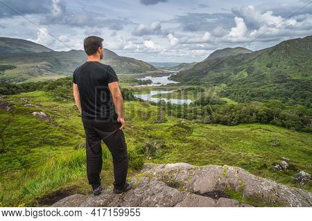 Middle Age Man Standing On A Rock And Admiring Beautiful Ladies View, One Of Iconic Irish Viewpoints