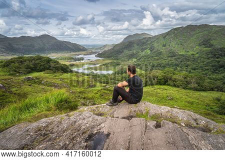 Middle Age Man Sitting On A Rock And Admiring Beautiful Ladies View, One Of Iconic Irish Viewpoints,