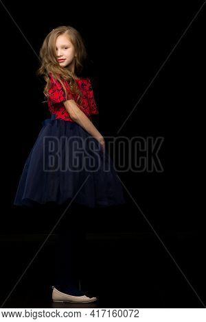 Beautiful Girl In A Tutu Dress Posing In The Studio On A Black B