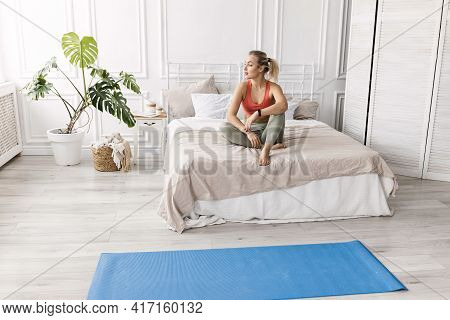 Beautiful Blonde-hair Woman In Stylish Sportswear Is Sitting On Bed, Resting After Morning Workout.