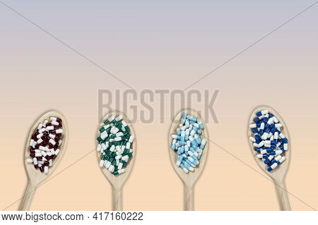 Wooden Spoons With Medicines To Symbolize How To Choose The Best Medicine For Your Disease