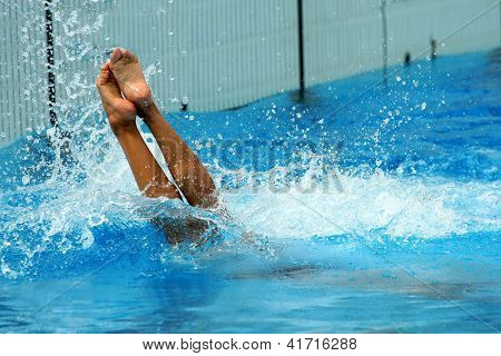 Woman jumping getting into water in diving action