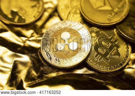 Gold Ripple Coins On A Golden Background. Trading On The Cryptocurrency Exchange. Cryptocurrency Sto