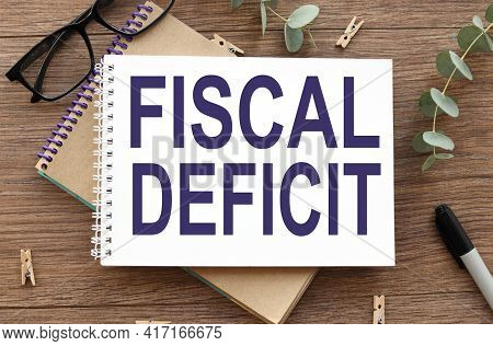 Text On White Paper On Wood Table Background. Fiscal Deficit