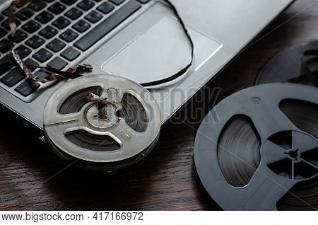 Old Reels Music Tapes Lie Next To The Laptop. Vintage Magnetic Audio Tape Reels On A Wooden Table. S