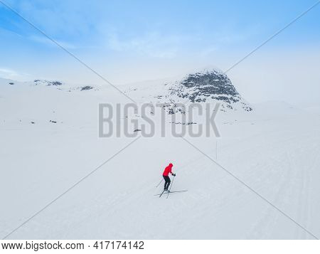 Cross Country Skier Traveling Across A Snowy Arctic Tundra In The High Mountains On A Cold Winters D