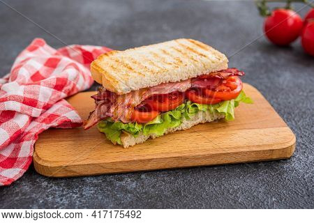 Blt Sandwich With Fried Bacon, Tomato And Lettuce On A Wooden Board On A Dark Concrete Background. A
