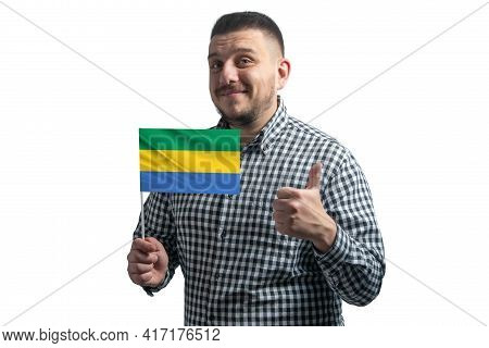 White Guy Holding A Flag Of Gabon And Shows The Class By Hand Isolated On A White Background. Like F