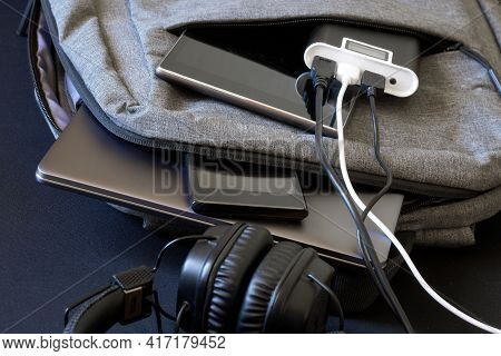 External Battery - The Powerbank Lies In A Gray Backpack Or Bag Along With A Laptop, Smartphone And