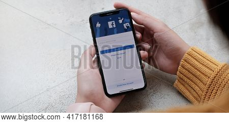 Chiang Mai , Thailand Apr 12 2021 : Woman Holding A Iphone X With Social Internet Service Facebook O