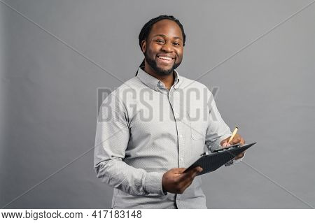 Cheerful African-american Young Man With Dreadlocks Holding A Folder, Taking Notes, Smiling Black Ma