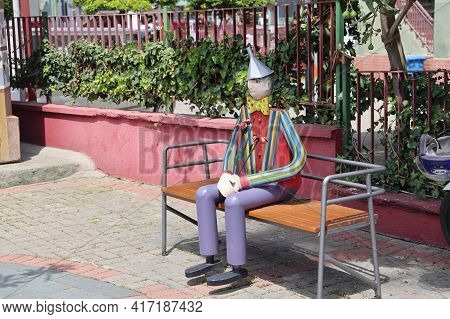 A Wooden Tourist In A Striped Shirt Sits On A Bench, Alanya, April, 2021