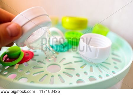 A Man Installs A Pacifier From A Baby Feeding Bottle Into A Sterilizer