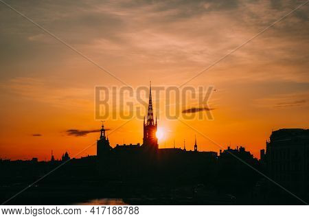 Stockholm, Sweden. Sunset Sun Shine Through Dark Silhouette Of Riddarholm Church In Stockholm Skylin