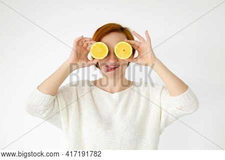 The Woman Stuck Out Her Tongue And Covered Her Eyes With Lemons. A Strange Face. Grimace. Woman In W