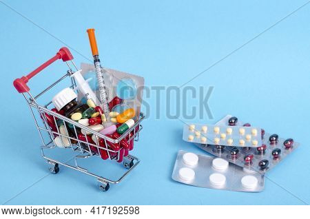 Buy Medicine. Shopping Basket With Various Medicinal, Pills, Tablets On Blue Background