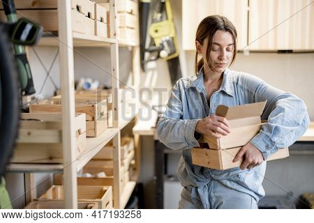 Young Handywoman Searching Some Working Tools On A Wooden Shelves In The Workshop. Concept Of Organi