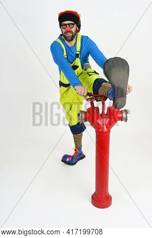 Holiday And Fun Concept. The Fire Clown Threw His Leg Over The Fire Pump.