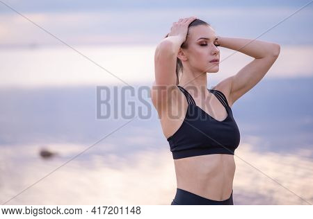 Portrait Of A Beautiful Fitness Model On A Background Of The Sea At Sunset