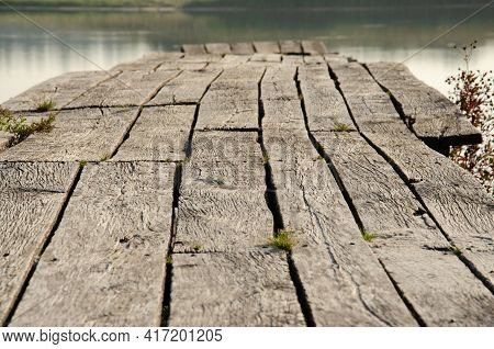 Old Wooden Pier On Lake. Selective Focus Surface Of Old Boards With Grass On Lake Pier. Wooden Textu