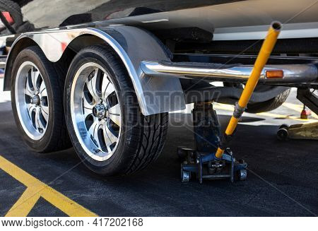 Close up view of a car jack lifting up a boat trailer that just had a new tire installed. Need new tires?