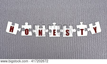 Honesty - Word Composed Of Paper White Puzzles On A Gray Background. Business Concept