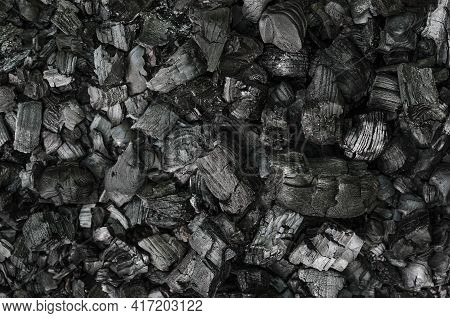Black And Gray Pieces Of Burnt Branches, In The Remains Of An Extinguished Fire. Charred Branches An